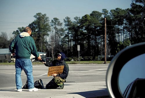 A man giving a homeless person some spare change.