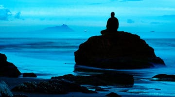 A monk sitting on a rock in the ocean in meditation.