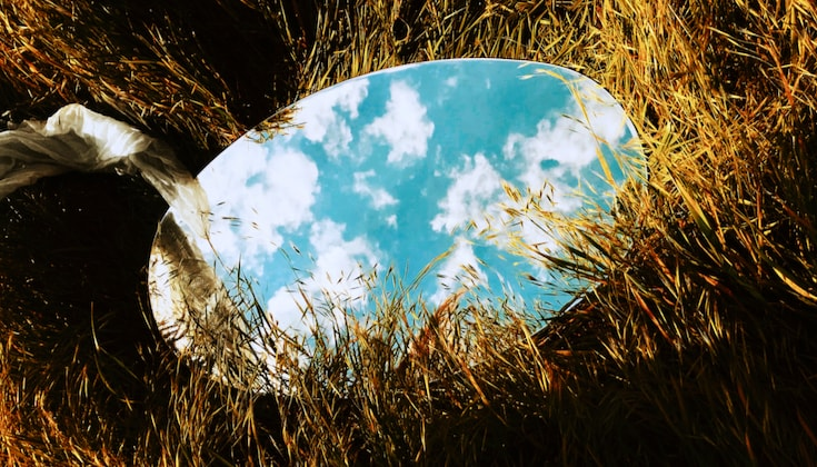 Mirror in tall grass reflecting the sky.