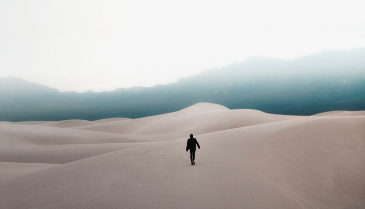 Person walking on cold sand dunes.