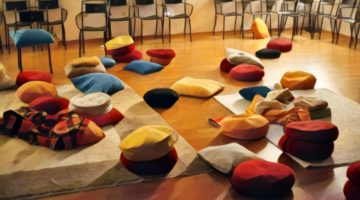Painting of meditation cushions scattered on floor.