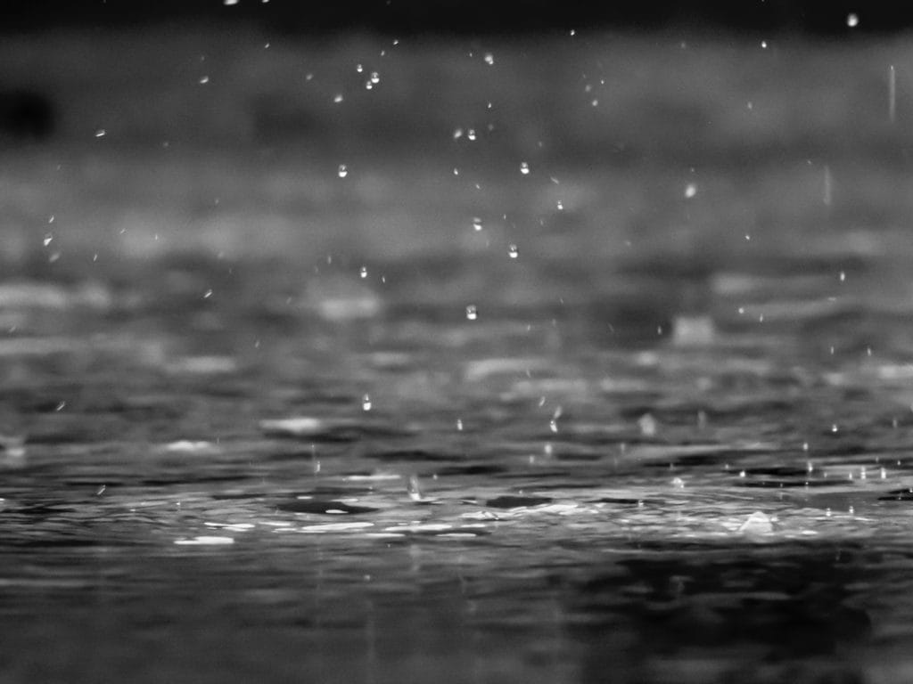 A black and white photo of raindrops hitting a body of water.