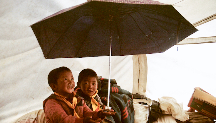 Two third-generation Tibetan refugees play with an umbrella inside a tent.