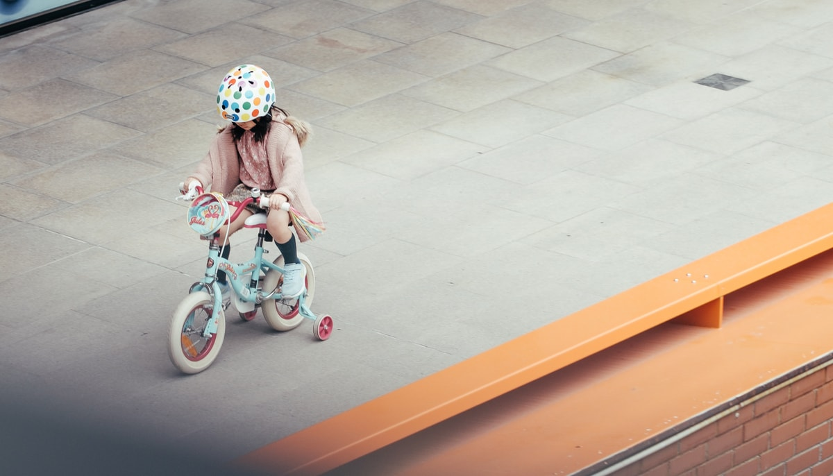 Girl on a bicycle with trainingwheels