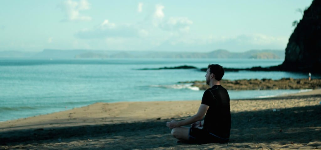 A man meditates on a beach. He is wearing a black t shirt and black shorts, and is looking out on the ocean.