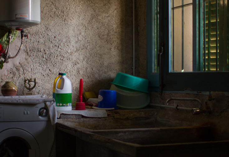 An image of a kitchen. There is a sink and a few dishes and cleaning supplies in the photo.