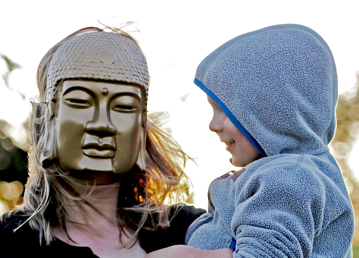 Mother wearing Buddha mask holding lughing child.