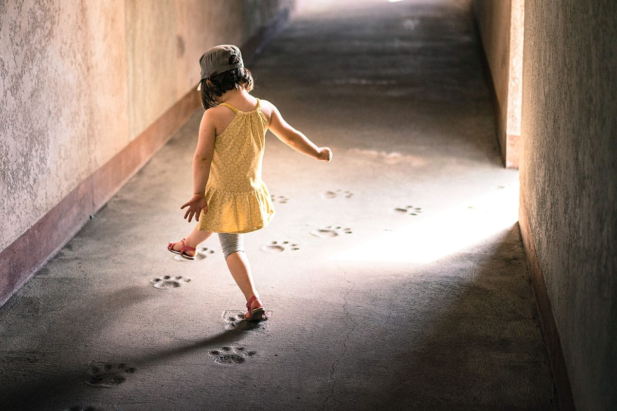 Young child following footprints in a hallway