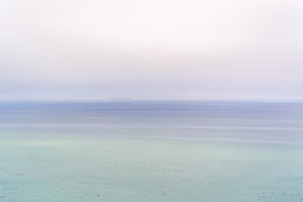 The sky and the ocean. The photo has a light periwinkle to seafoam green gradient.