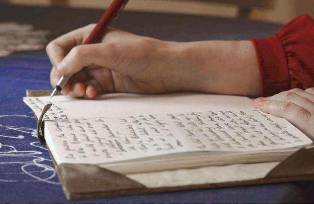 A hand writes on a journal with a pen.