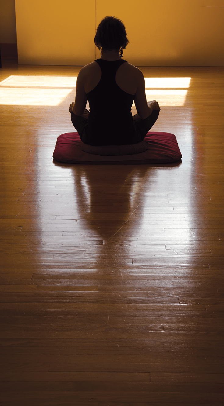 A woman sitting in meditation posture.