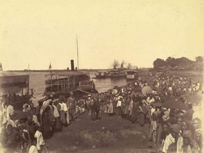 A crowd of people at a riverbank in an old photo.