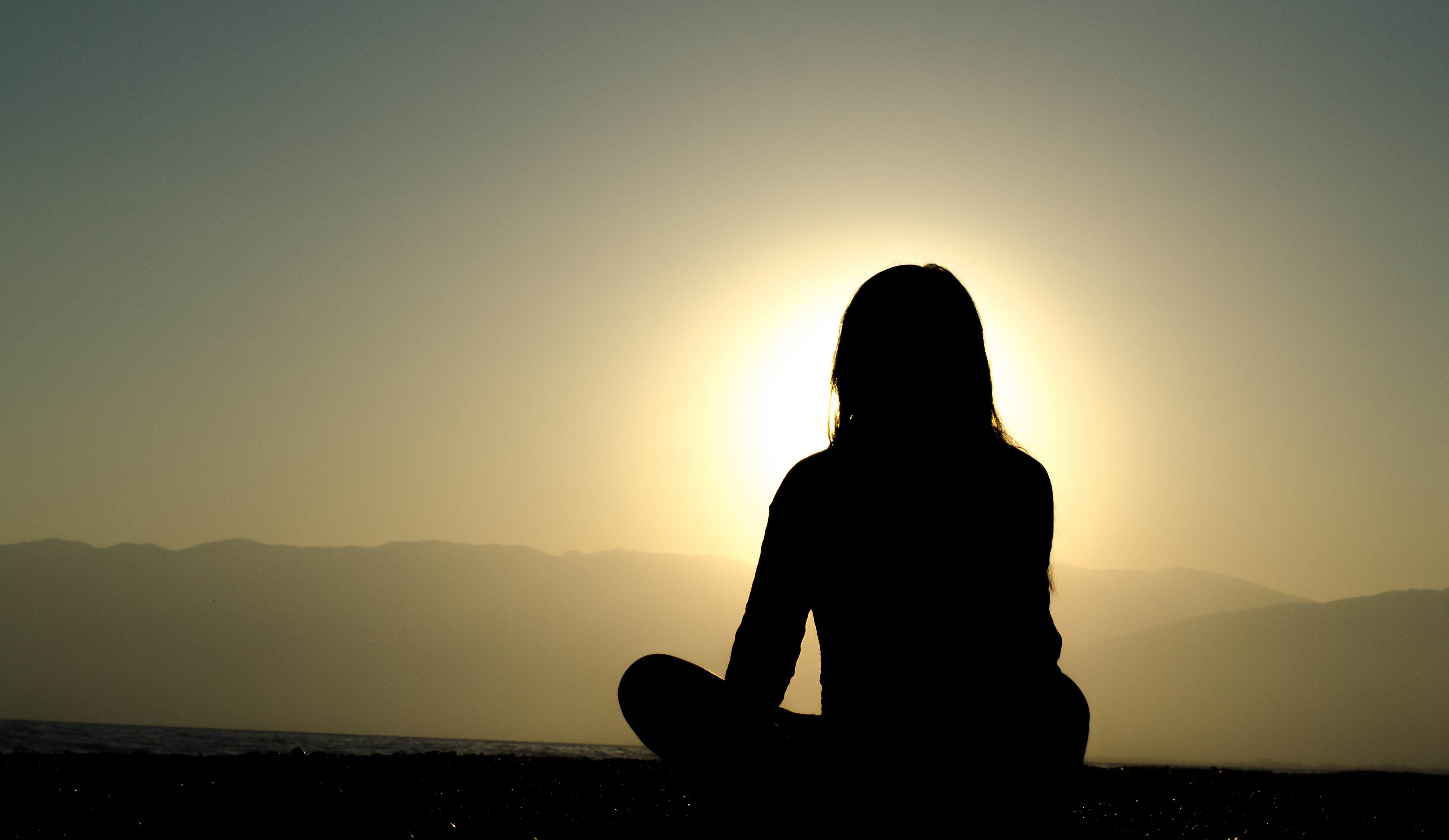 A person meditating in the sun.