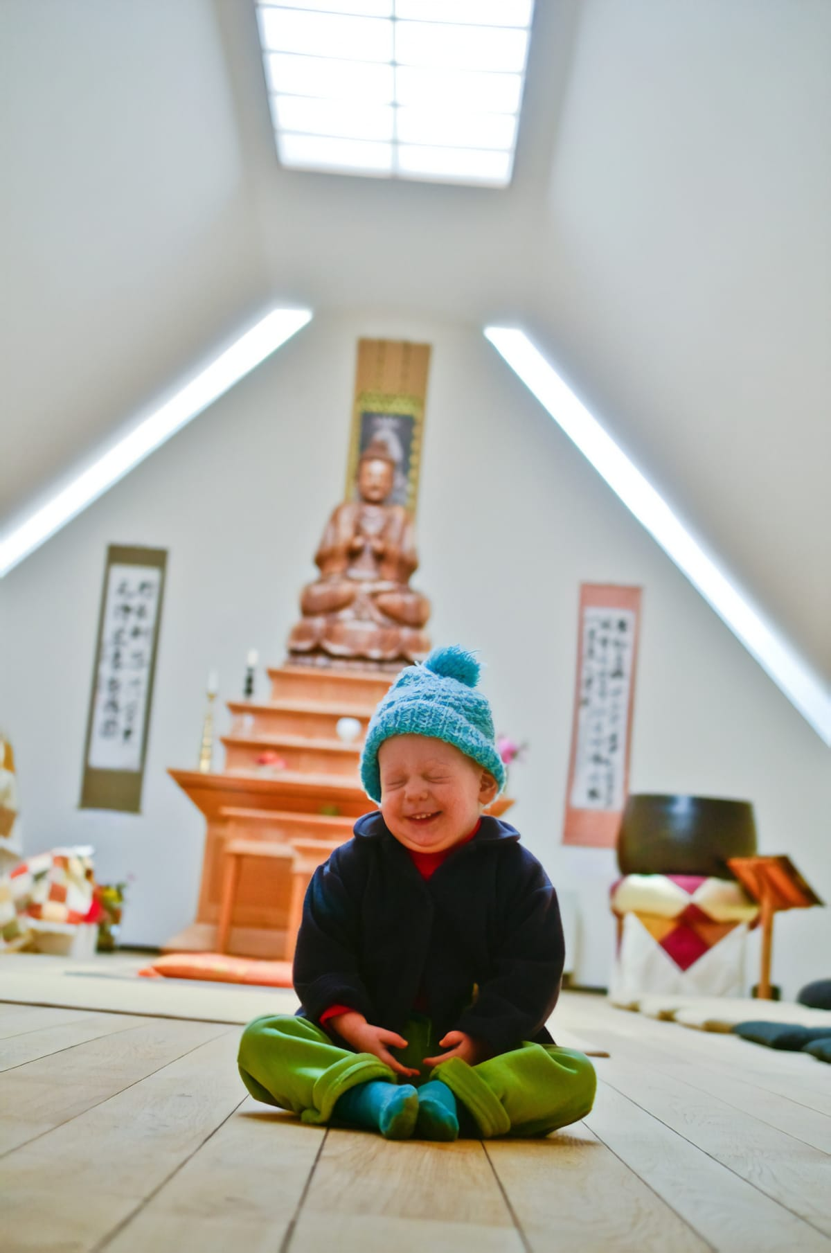 Little boy laughing in shrine room.
