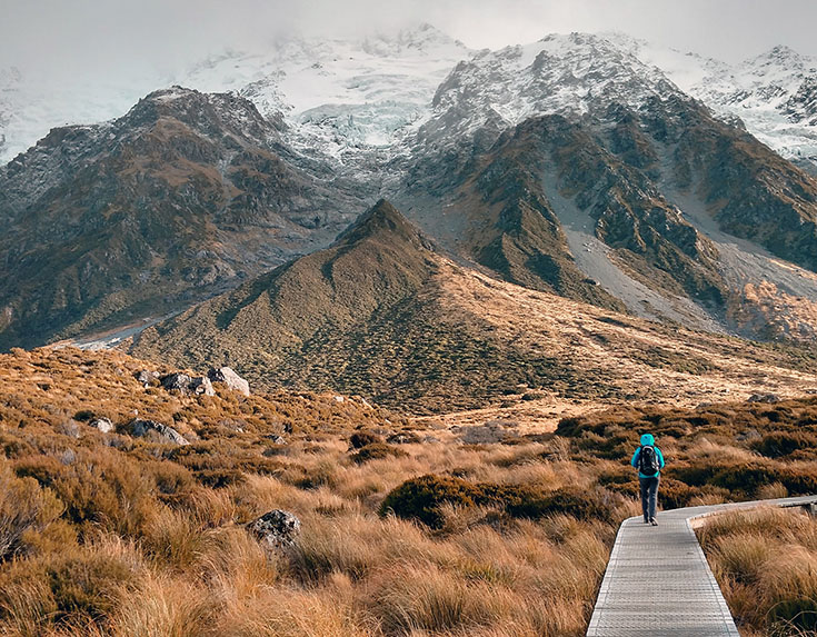 Person walking down a path with mountains in the background.
