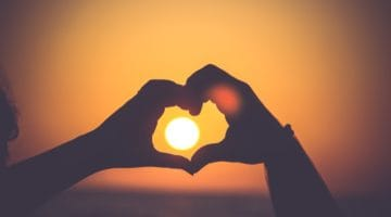 Hands in the shape of a heart around a setting sun