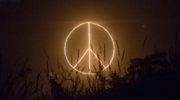 Peace sign written in light at night.