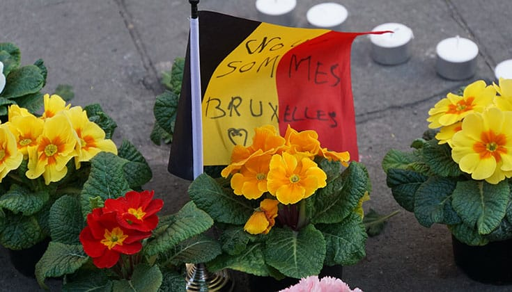"A Belgian flag amidst flowers, bearing the words, ""Nous sommes Bruxelles."""