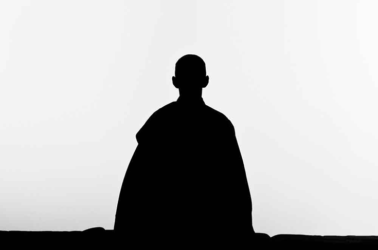 A silhouette of a person meditating.