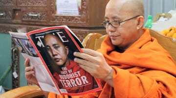 Radical Buddhist monk Ashin Wirathu reading a TIME magazine article about himself.