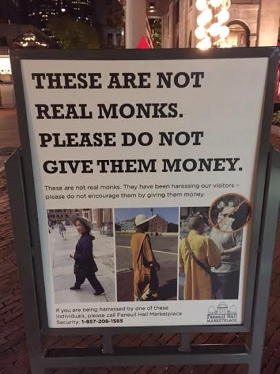 A sign at Boston's Faneuil Hall warns visitors against the fake-monk scam.