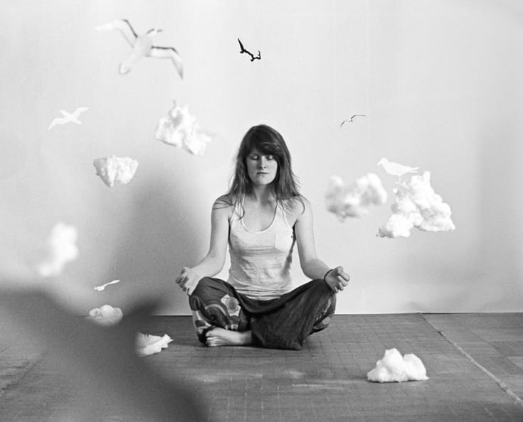 Woman meditating surrounded by clouds.