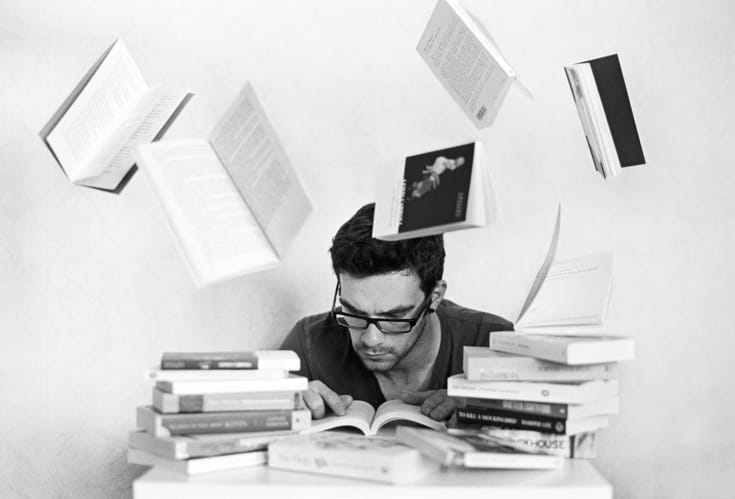 Man reading surrounded by books.