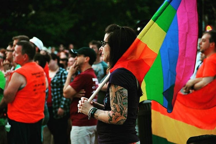 Demonstrator holding a pride flag at a vigil for Orlando.