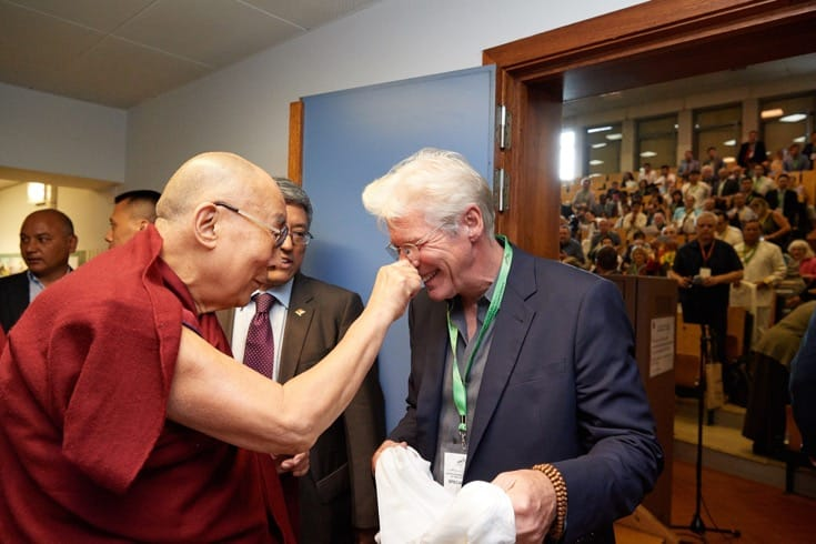 The Dalai Lama squeezes Richard Gere's nose.