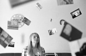 Woman sitting surrounded by pictures.