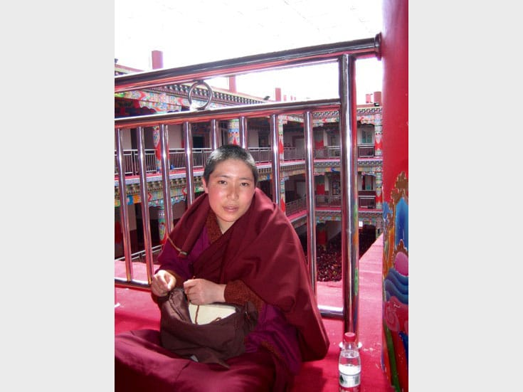 Nun studying inside Jomo Lhakhang. Photo by Holly Gayley.