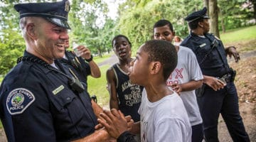 A cop laughs with children.