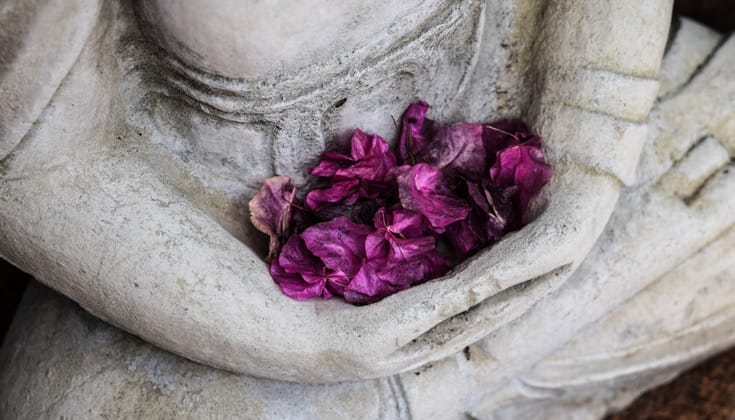 Buddha statue holding flowers.