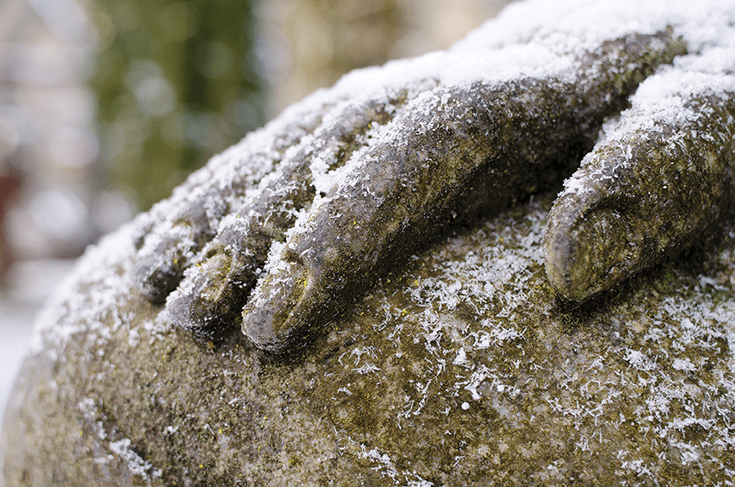 Hand of a Buddha statue covered in snowflakes. Photo by David Gabriel Fischer.