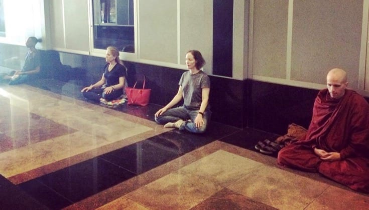 People meditating in a building lobby.