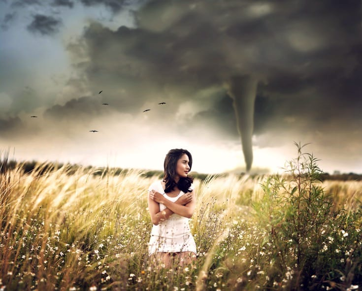 Women standing in front of a tornado.