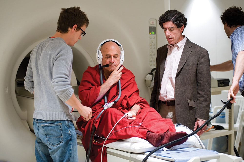 A technician (left) and neuroscientist Richard Davidson (right) prepare Ricard for an fMRI test at the Waisman Center at the University of Wisconsin- Madison. Ricard was a key collaborator in designing tests to document the long-term effects of meditation on the brain, and was their first subject. Photo by Jeff Miller / University of Wisconsin-Madison.