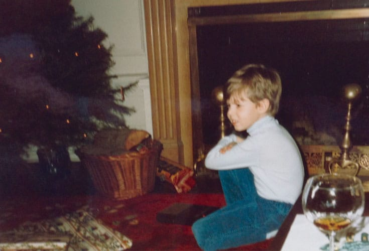 a young lodro rinzler next to his buddhist familys christmas tree