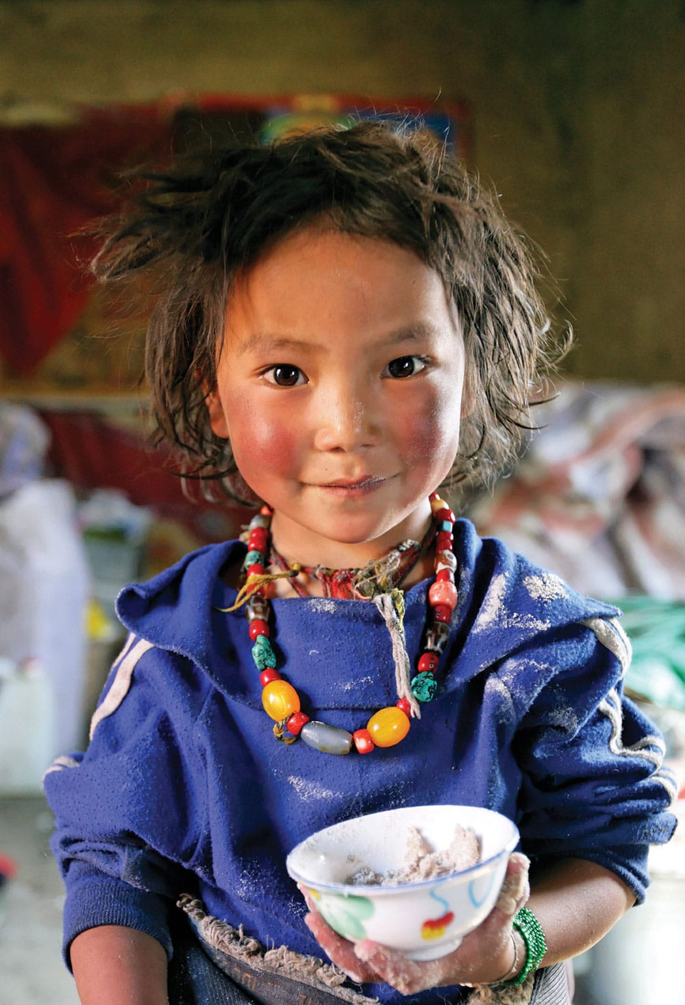 "Photo by Matthieu Ricard of a Tibetan girl. ""Her image,"" says Ricard, ""reminds me of the reason we work in Tibet and our mission to bring education and health to the Tibetan people and, especially, to young girls."