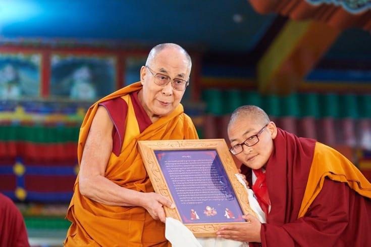 Nun presented framed text to the Dalai Lama.
