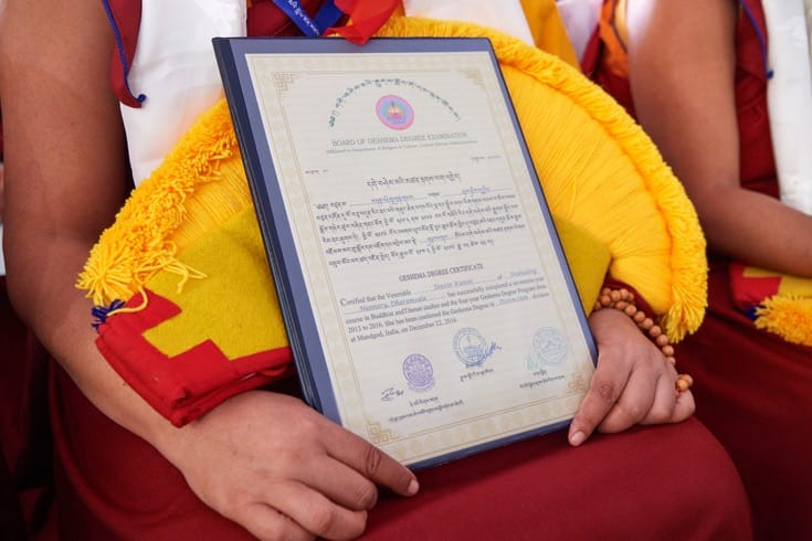 A nun holding her Geshema certificate.