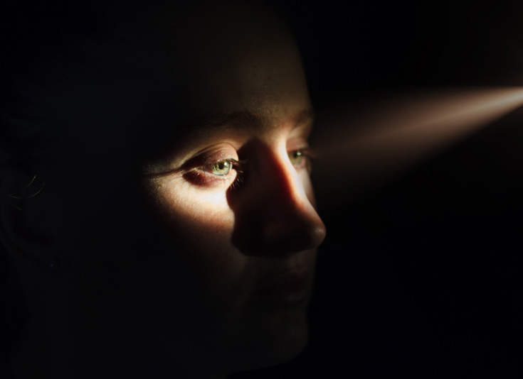 A woman in shadow with the light peeking over her eyes.