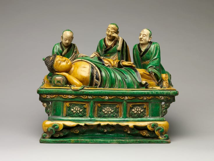 The Buddha lying down, dying, surrounded by grieving disciples, or arhats.
