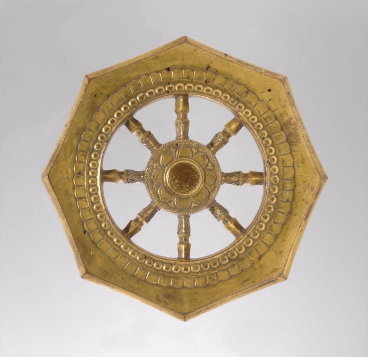 Wheel of Dharma. A bronze wheel with eight spokes and a lotus flower at its center.