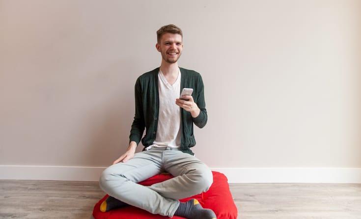Meditator holding an iPhone.