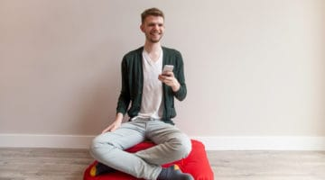 Meditator holding an iPhone.