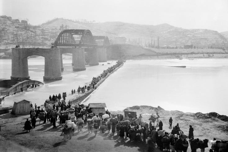 """Korean refugees crossing a provisional bridge over the Han River. December, 1950. Photo via the <a href=""""http://www.unmultimedia.org/s/photo/detail/103/0103323.html"""" target=""""_blank"""">United Nations</a>."""
