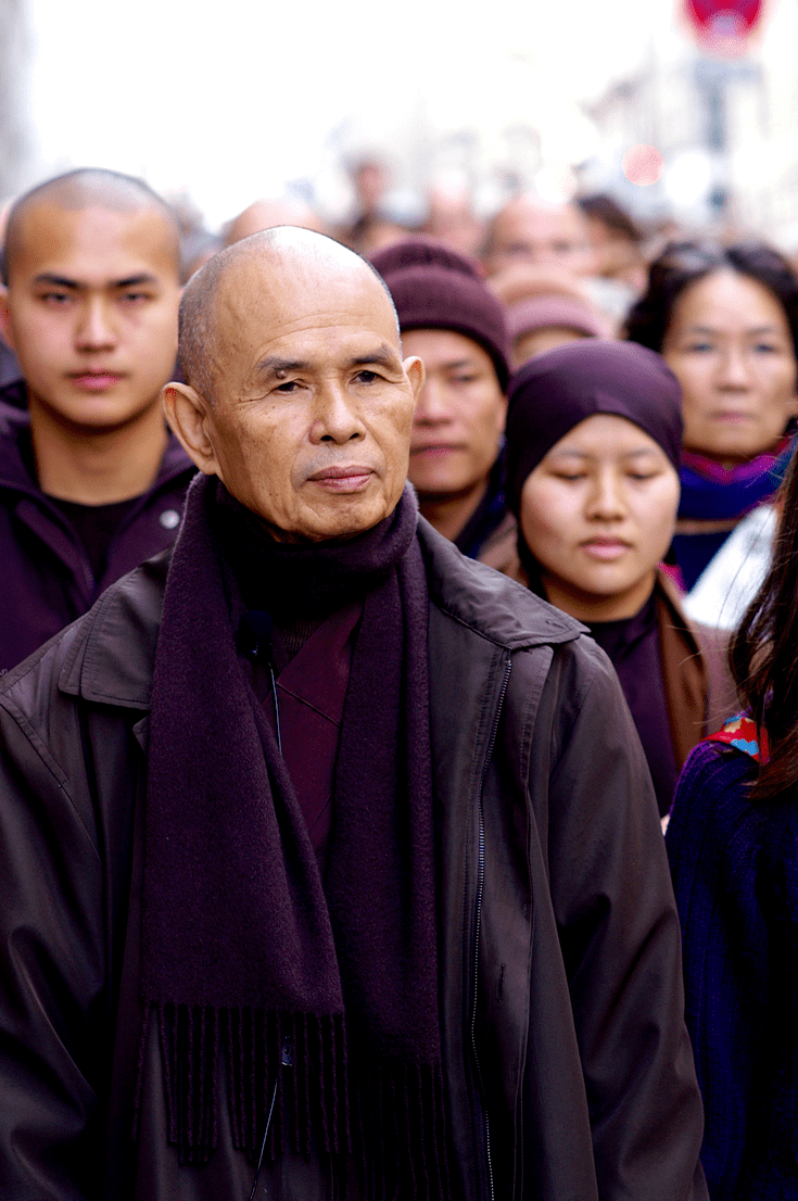 Thich Nhat Hanh walking with a crowd.