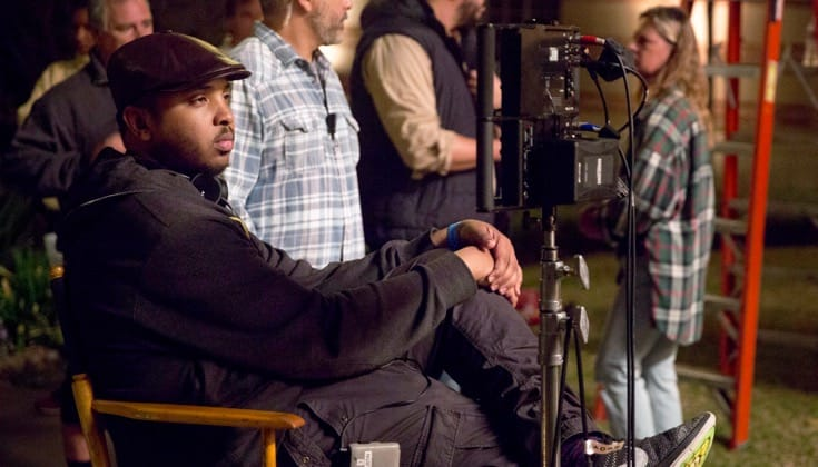 Justin Simien sitting in a director's chair on a studio set.