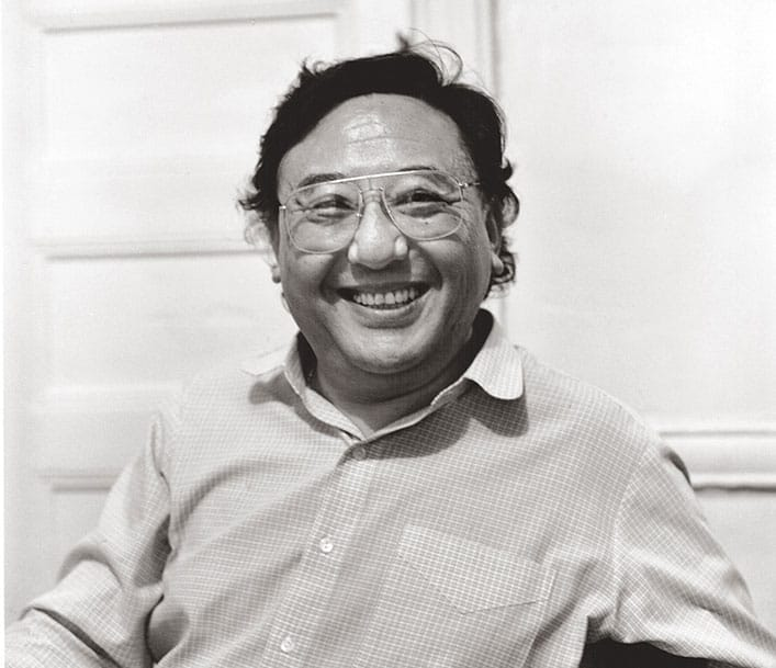 A black and white photo of a man smiling. He is wearing a checkered button up shirt and glasses.